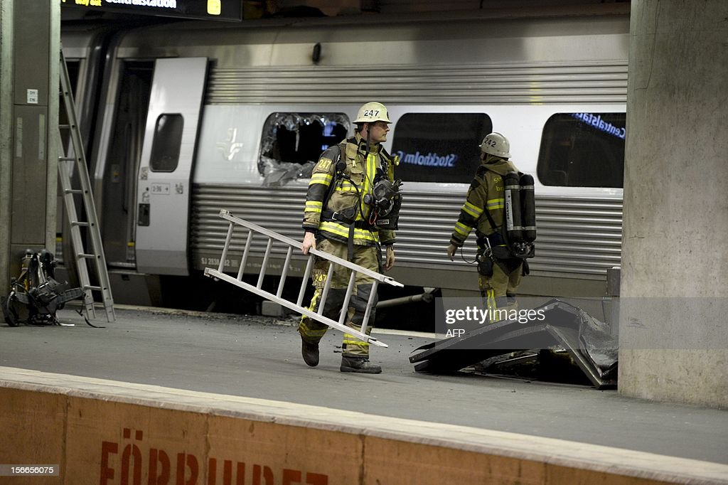 Firefighters walk along a burnt train carriage at the central station in Stockholm, on November 18, 2012. A fire on board an SJ X2000 train put a halt to all train traffic to and from the city as the station was ecacuated.