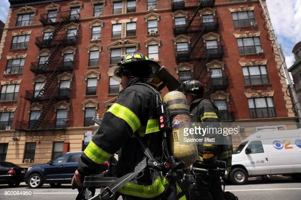 Firefighters walk near a Harlem subway station where a morning train derailment occurred on June 27 2017 in New York City Thirtyfour people suffered...