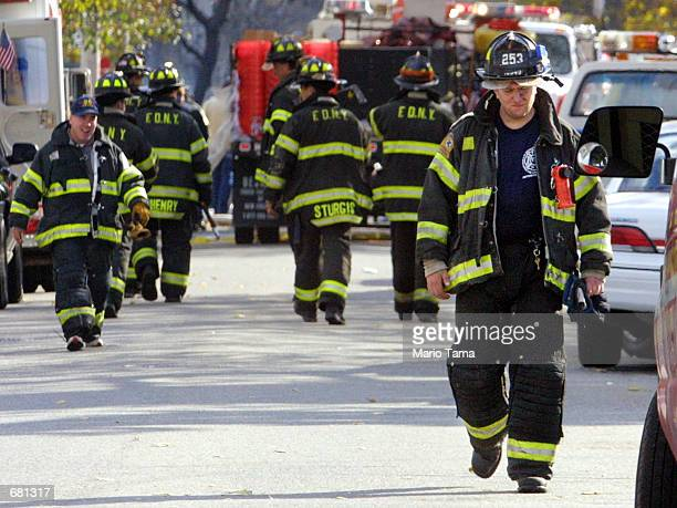 Firefighters walk near the American Airlines flight 587 crash site November 12 2001 at Rockaway Beach in Queens New York The plane carrying 255...