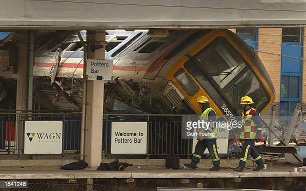 Firefighters walk past a derailed commuter train at Potter's Bar Railway Station May 10 2002 in Hertfordshire England The commuter train derailed...
