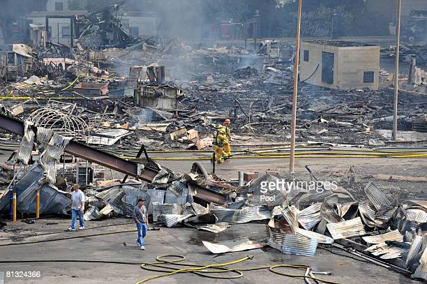 Firefighters walk past debris after approximately 400 firefighters from the Los Angeles area battled a huge fire on the backlot of Universal Studios...