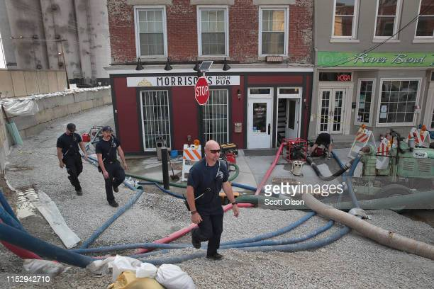 Firefighters walk past pumps and hoses working to keep floodwater from the Mississippi River out of the downtown area on May 31 2019 in Alton...