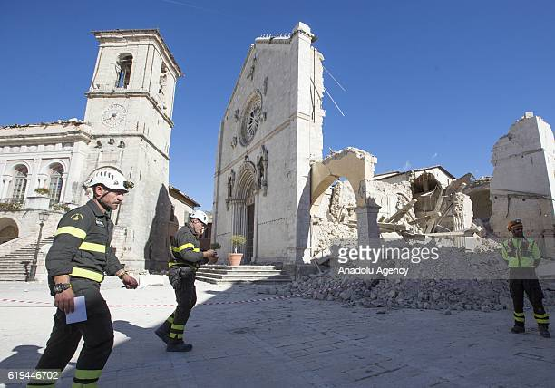 Firefighters walk past the damaged town hall, on left, and the collapsed St. Benedict Basilica, right, the day after the earthquake that hit central...