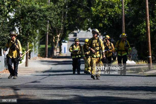 Firefighters walk through a neighborhood to inspect houses after the Clayton Fire burned through Lower Lake California on August 16 2016 A man was...