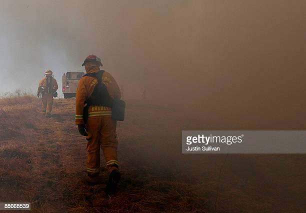 Firefighters walk through heavy smoke from a grass fire during a multiagency wildfire training drill June 24 2009 in Dublin California Fire...