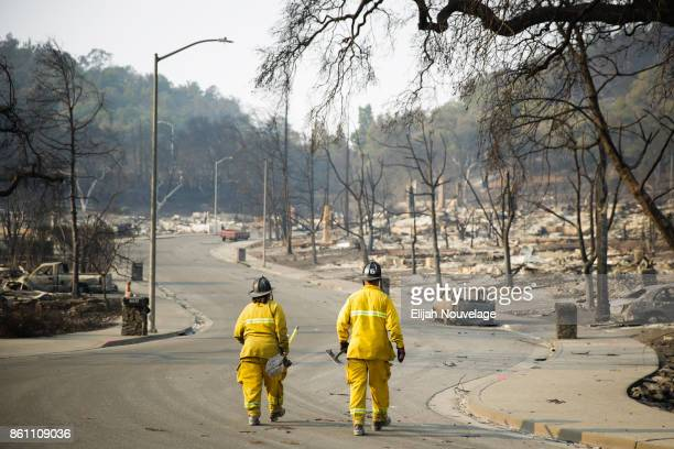 Firefighters walk through the Fountaingrove neighborhood on October 13, 2017 in Santa Rosa, California. Twenty four people have died in wildfires...