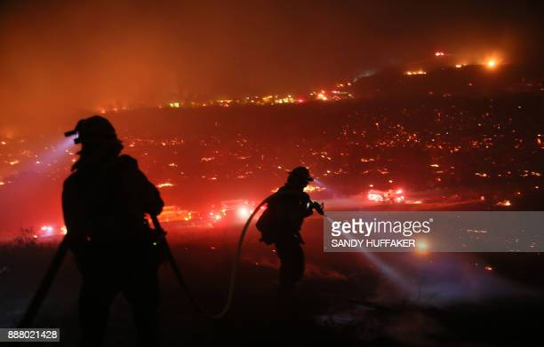 TOPSHOT Firefighters walk to the fire line at the Lilac fire in Bonsall California on December 7 2017 Local emergency officials warned of powerful...