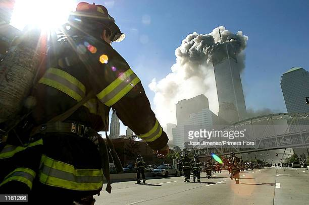 Firefighters walk towards one of the tower at the World Trade Center before it collapsed after a plane hit the building September 11 2001 in New York...