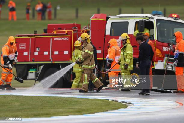 Firefighters wash oil off the track after a competitor in Moto3 spilt oil from turn one to turn nine during free practice for the 2018 MotoGP of...