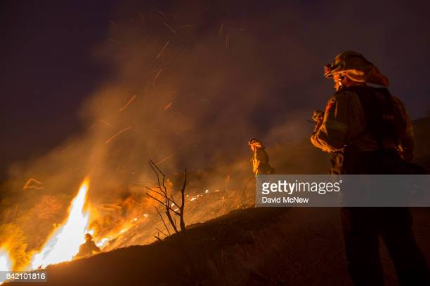 Firefighters watch a colleague emerge from fighting flames in chaparral brush using only a hand tool at the La Tuna Fire on September 2 2017 near...