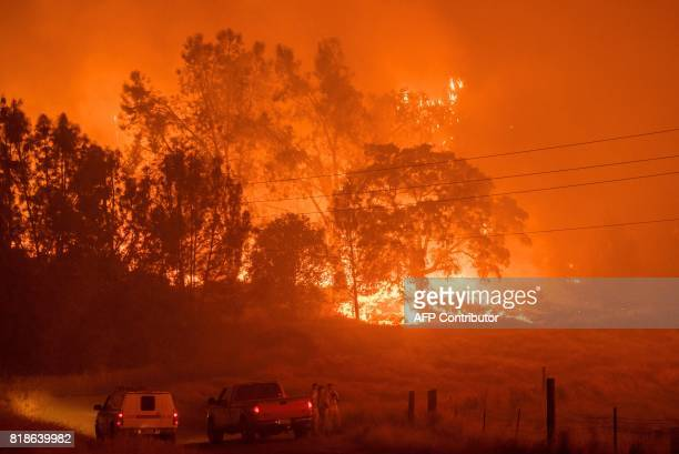 Firefighters watch approaching flames as the Detwiler fire rages on near the town of Mariposa California on July 18 2017 California has suffered...