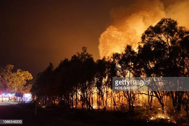 Firefighters watch as a blaze moves through Deepwater National Park in Queensland on November 28 2018 Thousands of people have been evacuated from...