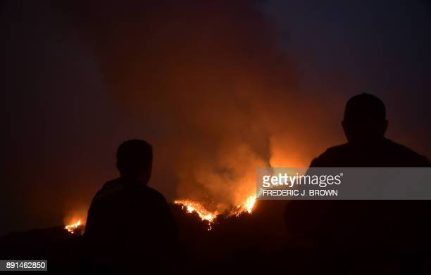 Firefighters watch as a fire erupts across a Romero Canyon hillside in Montecito California north of Santa Barbara on December 12 2017 Crews battling...