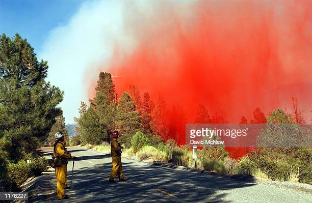 Firefighters watch as an airtanker drops a load of fire retardant to keep the outofcontrol McNally fire from jumping a road July 25 2002 in the...