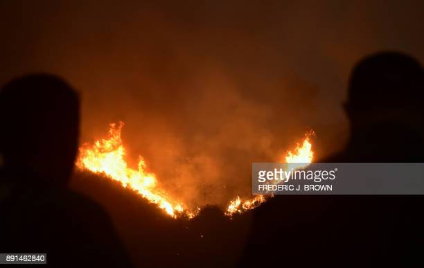 Firefighters watch as fires burn across Romero Canyon hillside in Montecito California north of Santa Barbara on December 12 2017 Crews battling...