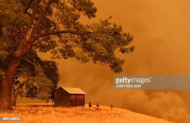 TOPSHOT Firefighters watch as flames from the County Fire climb a hillside in Guinda California on July 1 2018 Californian authorities have issued...