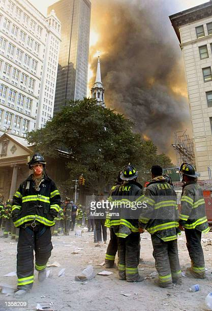 Firefighters watch as smoke rises from the site of the World Trade Center collapse September 11, 2001 in New York City after two hijacked airplanes...