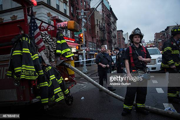 Firefighters watch as their coworkers battle a blaze caused by an explosion that forced two buildings to collapse on Second Avenue in Manhattan's...