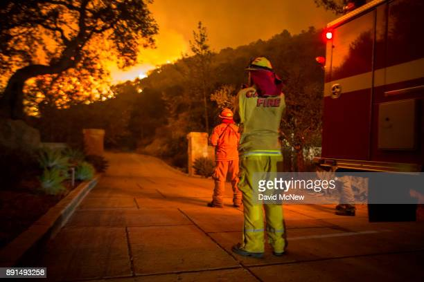 Firefighters watch flames as the Thomas Fire approaches homes on December 12 2017 in Montecito California The Thomas Fire has spread across 365 miles...