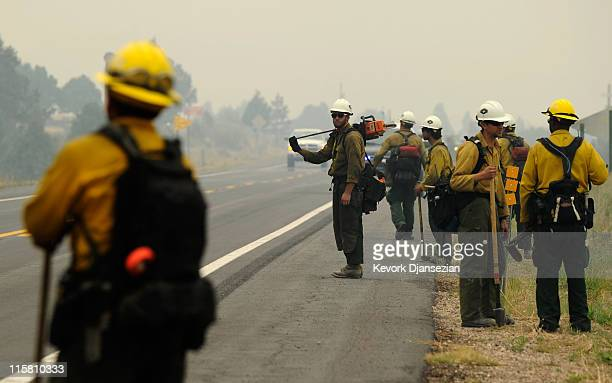 Firefighters watch from across the road after setting a backburn on Highway 191 in an attempt to control a raging wildfire on June 10 2011 in...