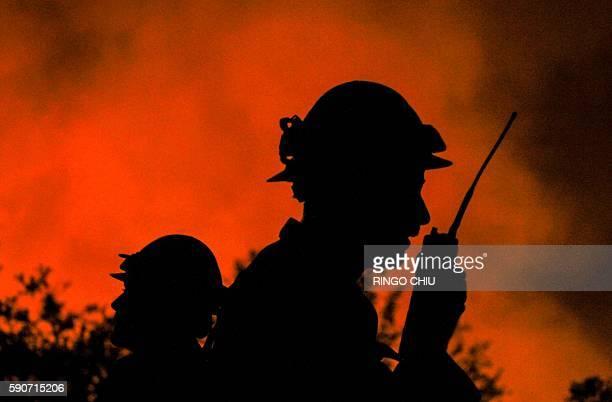 Firefighters watch the Blue Cut wildfire burning near Cajon Pass north of San Bernardino California on August 16 2016 A rapidly spreading fire raging...