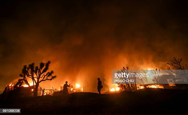Firefighters watch the Blue Cut wildfire near Cajon Pass north of San Bernardino California on August 16 2016 A rapidly spreading fire raging east of...