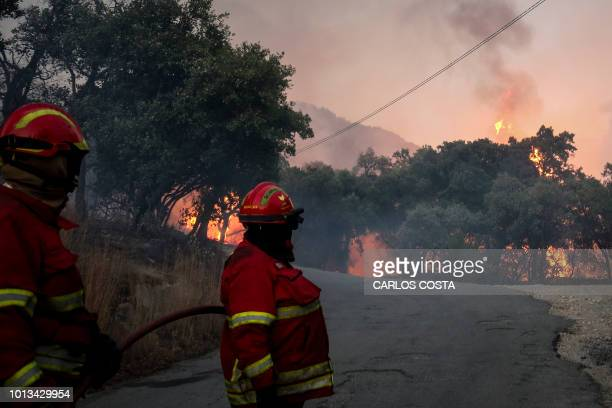 Firefighters watch trees burning in flames as they combat a wildfire close to Monchique in the Portuguese Algarve, on August 8, 2018. - Wildfires...