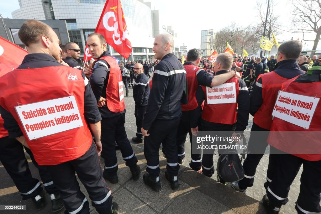 Firefighters wear jackets with a writing reading 'Suicide at work. Firefighters upset' during a demonstration of French firemen against staff reduction in Paris on March 14, 2017. / AFP PHOTO / Jacques DEMARTHON