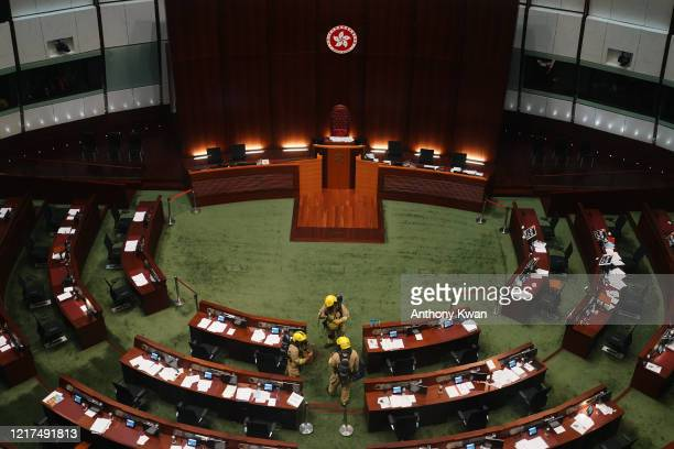 Firefighters wearing gas masks check the main chamber of the Legislative Council after a prodemocracy lawmaker threw an object during the thrid...