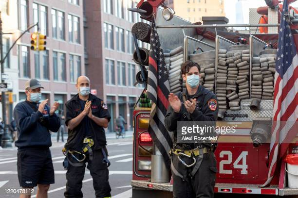 Firefighters wearing protective masks applaud healthcare workers during the 7PM nightly cheer in front of the Lenox Health Greenwich Village Hospital...