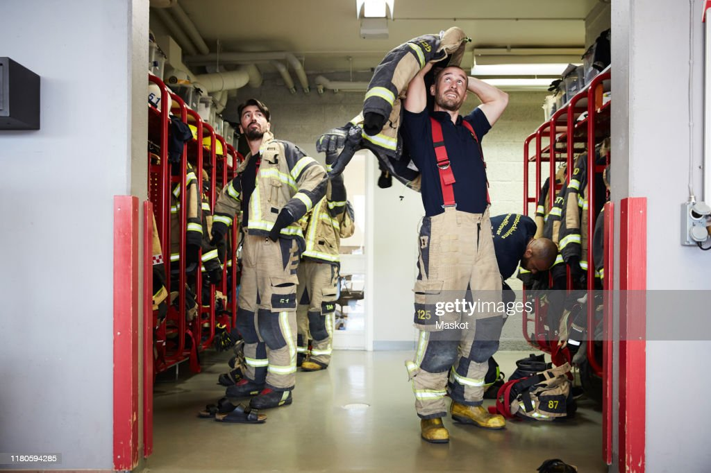 Firefighters wearing protective workwear in locker room while looking up at fire station : Stock Photo