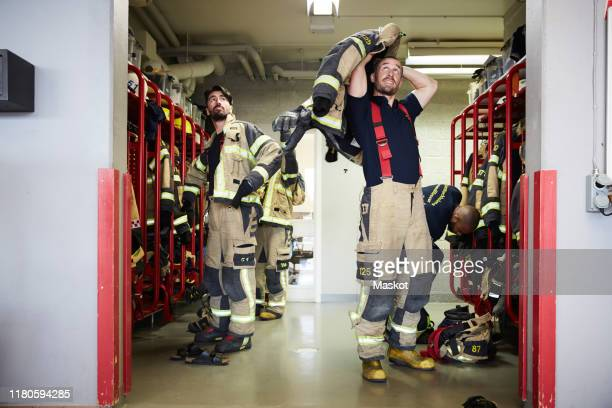 firefighters wearing protective workwear in locker room while looking up at fire station - fire station stock pictures, royalty-free photos & images