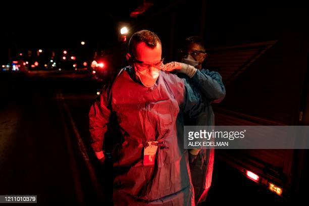 TOPSHOT Firefighters with Anne Arundel County Fire Department put on enhanced PPE prior to treating a potential COVID19 patient on April 22 2020 in...