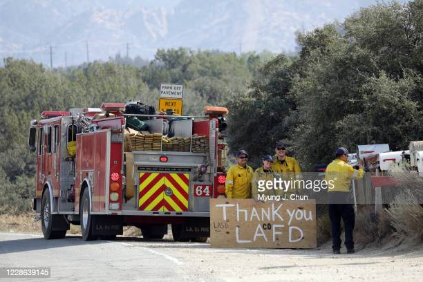 Firefighters with LA County Station 64 in San Dimas Eric Miller left Justine Oyler and Patrick Shaw wait as Victor Le sets the camera on a mailbox...