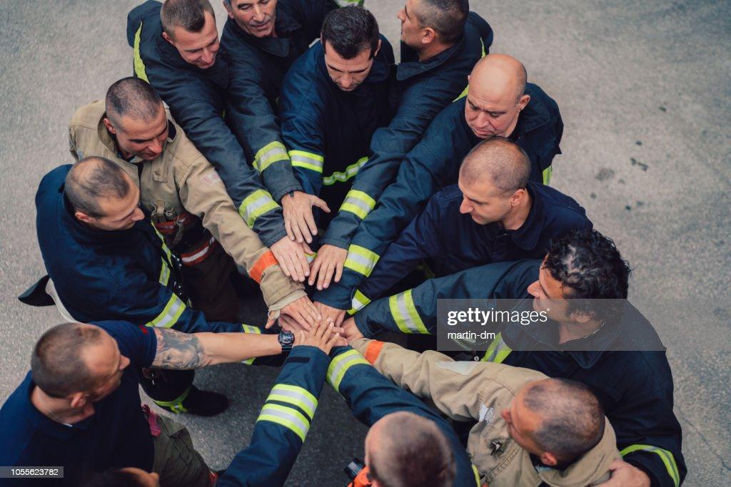 Bombeiros com mãos empilhadas : Foto de stock