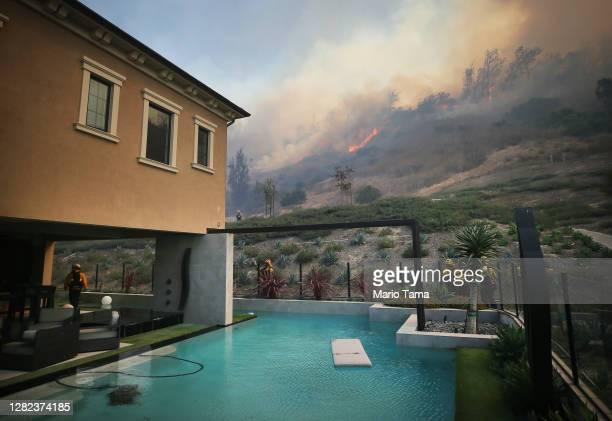 Firefighters work as the Silverado Fire burns toward a home in Orange County on October 26, 2020 in Irvine, California. The fire has prompted...