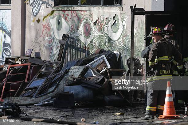 Firefighters work at the scene following an overnight fire that claimed the lives of at least nine people at a warehouse in the Fruitvale...