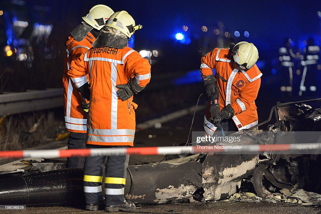 Firefighters work at the scene of a helicopter wreckage after it crashed onto the A6 highway on January 10, 2013 near Schwabisch Hall, Germany. According to police the helicopter struck a nearby power line and exploded, killing the pilot and leaving one vehicle driver with minor injuries.