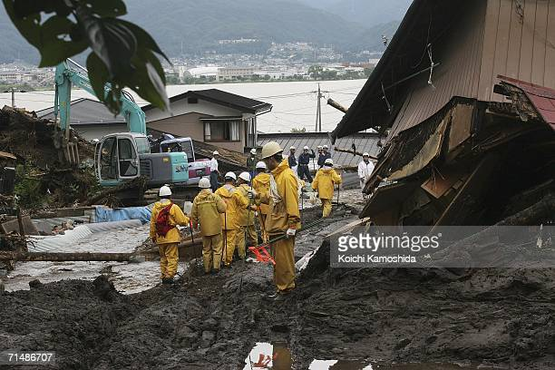 Firefighters work at the scene of a mudslide in Okaya city after heavy rain July 20, 2006 in Nagano, Japan. Torrential rains in central and western...