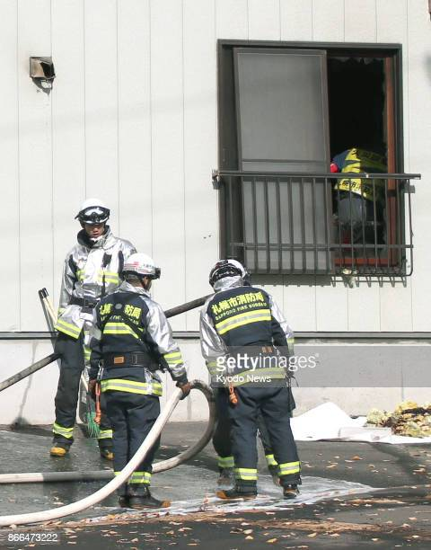 Firefighters work at the scene of an apartment fire in Sapporo on Oct 26 in which two infants aged 2 and 3 died and their mother was being treated...