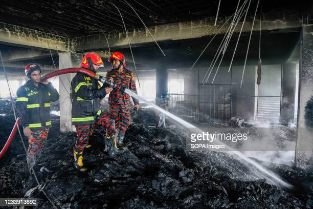 Firefighters work at the site of a fire that broke out on Thursday night at Hashem Foods Ltd factory in Rupganj, Narayanganj district, on the...