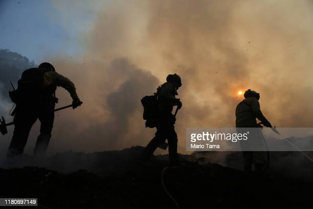 Firefighters work during a flare up at a mulch supplier during the Saddleridge Fire on October 12 2019 in Sylmar California The winddriven fire has...