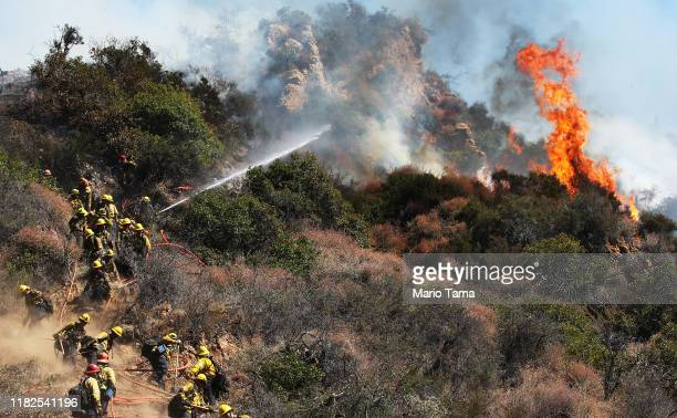 Firefighters work during a wildfire threatening nearby hillside homes in the Pacific Palisades neighborhood on October 21 2019 in Los Angeles...