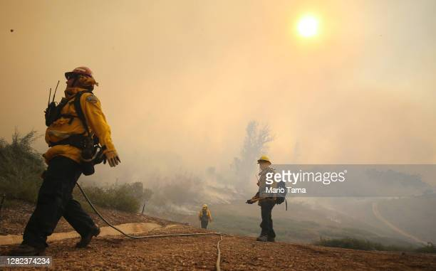 Firefighters work during the Silverado Fire in Orange County on October 26, 2020 in Irvine, California. The fire has prompted mandatory evacuations...