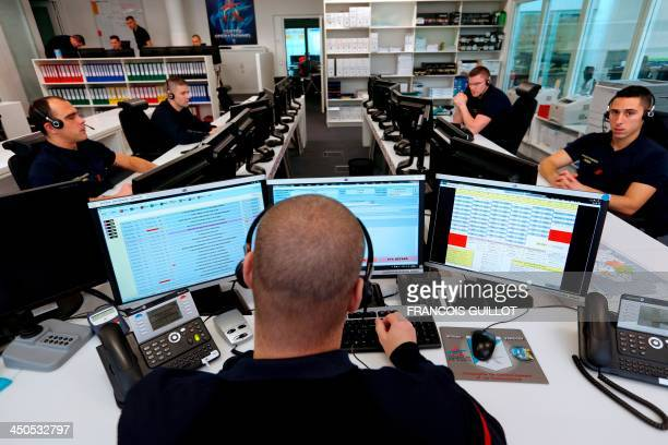 Firefighters work in a call centre at Paris fire brigade's operational centre in the Champerret fire station on November 19 2013 AFP PHOTO / FRANCOIS...