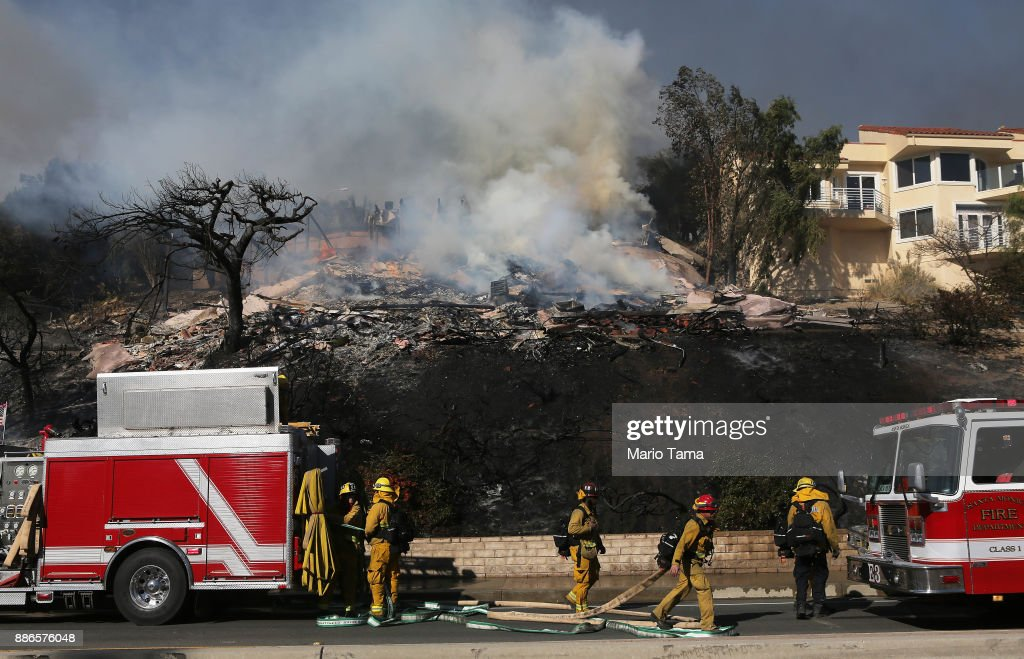 Firefighters work in front of a home destroyed by the Thomas Fire on December 5, 2017 in Ventura, California. Around 45,000 acres have burned in the fire forcing thousands to evacuate and destroying 150 structures.