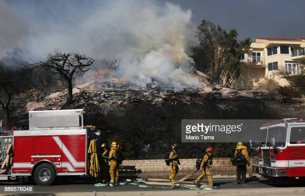 Firefighters work in front of a home destroyed by the Thomas Fire on December 5 2017 in Ventura California Around 45000 acres have burned in the fire...