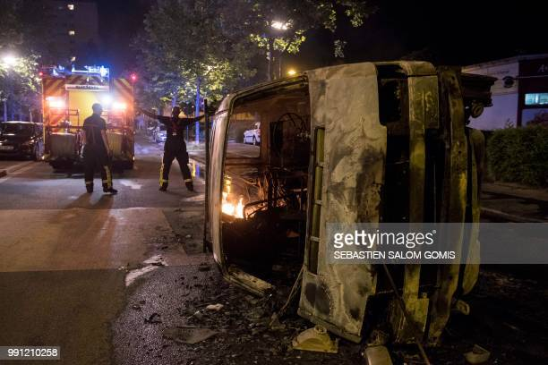 TOPSHOT Firefighters work near a burnt car in the Breil neighborhood of Nantes early on July 4 2018 Groups of young people clashed with police in the...