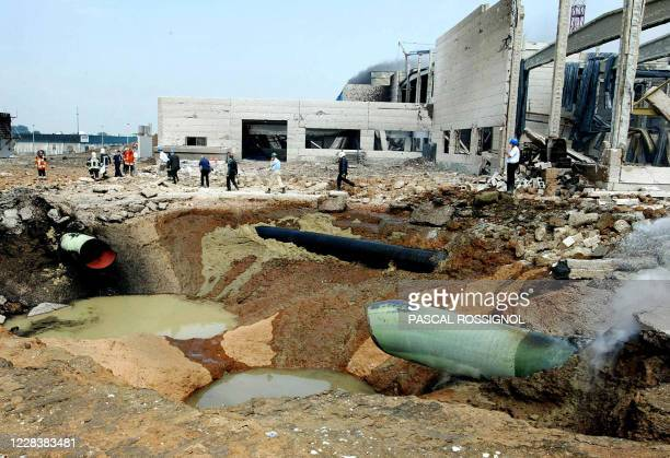 Firefighters work near a large crater made after a gas pipeline was ruptured and exploded at an industrial estate in Ghislenghien, southern Belgium,...