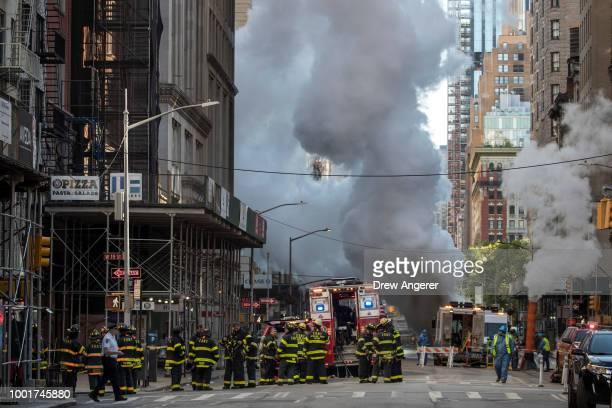 Firefighters work near the scene of a steam pipe explosion on Fifth Avenue near the Flatiron District July 19 2018 in New York City Buildings were...